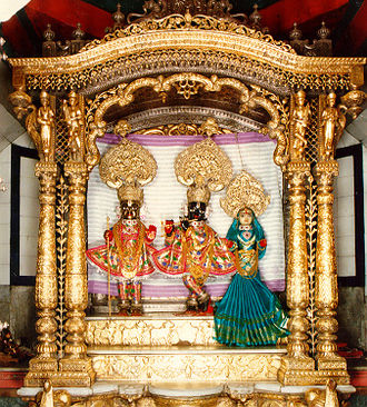 Swaminarayan - Madan Mohan and Radha (centre and right) with Swaminarayan in the form of Hari Krishna (left), installed by Swaminarayan on the central altar in Dholera (1826)
