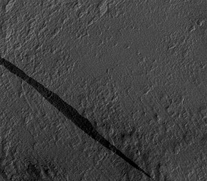 Dark slope streak - Dark slope streaks often do not affect the underlying texture of the slope on which they form, indicating that the disturbance causing the streak is superficial. Image is portion of MOC-N/A frame M09/00039, based on Sullivan et al., 2001, p. 23,612, Fig. 5a. The streak here is 1.3 km long.