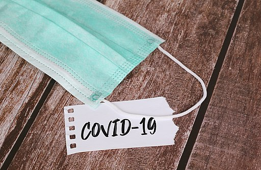Medical protective face masks with COVID-19 text on a note