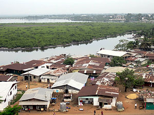 Environmental issues in Liberia - Dwellings along the Mesurado River in Monrovia. Discarded plastics can be seen washed up on the bank opposite the buildings.