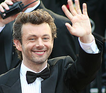 Michael Sheen, a caucasian male in his early-40s with dark curly hair, wears a black suit and white shirt with a black bow-tie. He smiles and waves with his left hand.