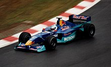 A figure, wearing a helmet with a white and aqua design, is driving a Formula One car that is of a dark blue and aqua colour scheme. He is holding both hands on a steering wheel, turning right.