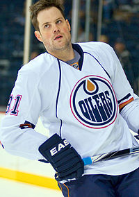 Mike Comrie skating on the ice holding his hockey stick as an Edmonton Oilers team member.