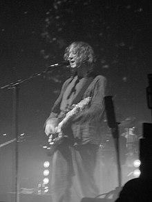 Nigra-kaj-blanka-bildo de viro elfaranta sur-scenejon per elektra gitaro kaj kantadon en mikrofonon.