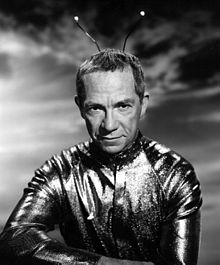 A black-and-white photo of Walston as a Martian, with a shiny suit and antenna on his head