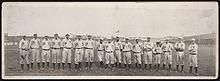Een enkele rij mannen in witte honkbaluniformen met hoge sokken en witte honkbalpetten die op een honkbalveld staan;  op hun uniformen stond 'NY' op de borst.