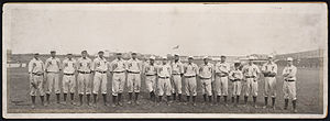 "A single row of men in white baseball uniforms with high socks and white baseball caps standing on a baseball field; their uniforms read ""NY"" across the chest."