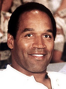 A black man smiling at a camera while wearing a white shirt.