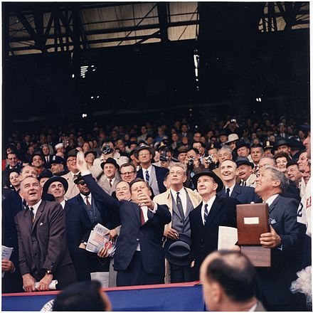 Opening Day of 1961 baseball season. President Kennedy throws out the first ball at Griffith Stadium, the home field of the Washington Senators, as LBJ and Hubert Humphrey look on. Opening Day of 1961 Baseball Season. President Kennedy throws out first ball. (first row) Vice President Johnson... - NARA - 194197.jpg