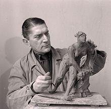 Lo scultore Angelo Ferreri modella un'opera in creta nel suo studio. Foto di Paolo Monti, 1965
