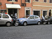 Parking in central Rome, Italy. Although the cars leave a space, this is soon filled with a scooter or motorcycle making it impossible for the cars to leave.
