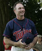"A smiling man wearing a navy-blue baseball jersey with ""Twins"" across the chest in red script"
