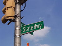 A green street sign reading State Highway attached to a traffic light pole.