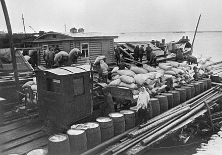 Supplies being unloaded from a barge on Lake Ladoga to a narrow-gauge train in 1942 RIAN archive 310 Foodstuffs for Leningrad.jpg