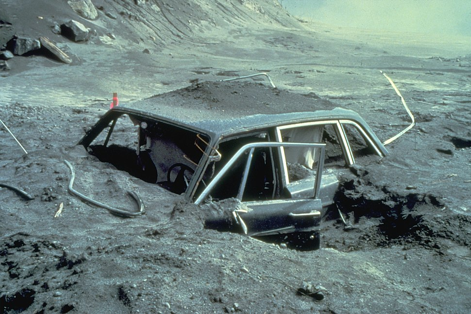 Heavily damaged car embedded in gray soil