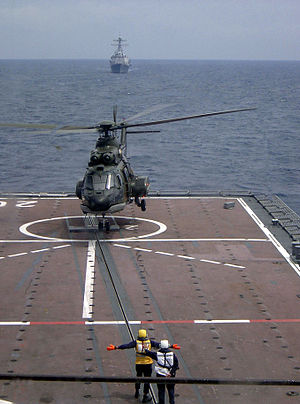 Endurance-class landing platform dock - A Republic of Singapore Air Force Super Puma takes off from the flight deck of Resolution. Visible in the foreground is the ASIST system
