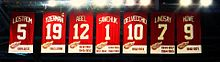 "The banners of seven retired numbers. The banners, from left to right, read ""Lidström 5"" ""Yzerman 19"" ""Sawchuk 1"" ""Delvecchio 10"" ""Lindsay 7"" ""Abel 12"" ""Howe 9"". The Yzerman banner has a small C at the top right corner."