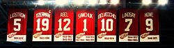 "The banners of seven retired numbers. The banners, from left to right, read ""Lidstrom 5"" ""Yzerman 19"" ""Sawchuk 1"" ""Delvecchio 10"" ""Lindsay 7"" ""Abel 12"" ""Howe 9"". The Yzerman banner has a small ""C"" at the top right corner."