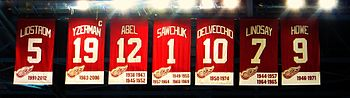 The banners for retired numbers that hang at Joe Louis Arena. The banners read, from left to right − LIDSTROM 5 − YZERMAN 19 − SAWCHUK 1 − DELVECCHIO 10 − LINDSAY 7 − ABEL 12 − HOWE 9