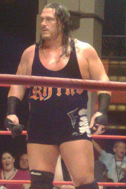 An adult white male wearing black standing in a wrestling ring.