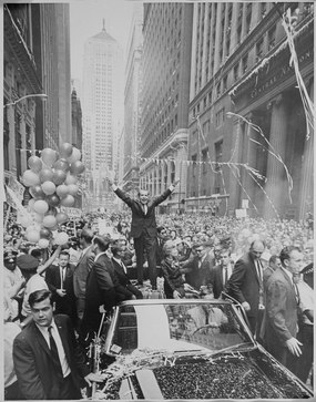 "Nixon stands atop a motorcade vehicle, smiling, holding up his ""v-sign"" to a massive crowd on a Chicago street"