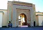 A large, architecturally detailed entrance to a big palace. Several guards are posted out front.