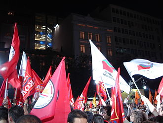 Syriza - Coalition supporters in a 2007 rally in which flags of Synaspismós, AKOA, DIKKI and Kokkino can be seen as well as those of the coalition itself