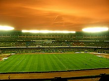 A large football stadium which is roughly 75% full. There are footballers on the pitch, most of whom are on the right side of the stadium. The team on the left, East Bengal are wearing red while Bayern Munich, right, are wearing black. The floodlights are on and the sky appears to be orange.