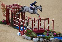 A gray horse, ridden by a woman, in mid-air over a red and white striped fence.