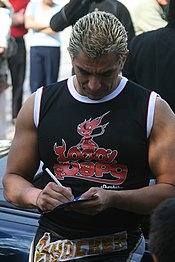 A male with blond hair wearing a black shirt signing an autograph.