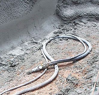 Shotcrete - Shotcrete nozzle with 75 mm concrete hose from line pump and 20 mm compressed air line.