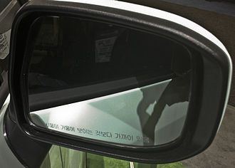 "Objects in mirror are closer than they appear - Wing mirror on a South Korean-specification vehicle. Legend in Korean reads ""Objects in mirror are closer than they appear""."