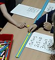 Six year olds in class using a Cuisenaire track to explore multiplication.jpg