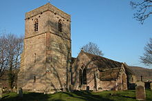 A stone church seen from the southwest, with a tower on the left, and a gabled south aisle and a porch on the right