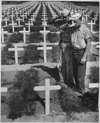 Two US Coast Guardsmen pay homage to their comrade killed in the Ryukyu Islands. Standing in the grassy sod bordering row upon row of white crosses in an American cemetery, two dungaree-clad Coast... - NARA - 513229.tif