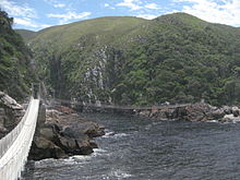 Suspension bridge at Storms River - River mouth between two ragged cliffs with some greenery, with the suspension bridge in the foreground