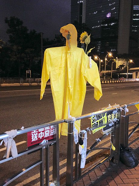 A straw man in yellow raincoat resembling that worn by the first protester who jumped to his death from Pacific Place is still hung over the railing outside the suicide scene in honour of him. Straw Man in Yellow Raincoat.jpg