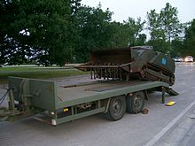 A self-propelled machine being loaded onto a vehicle transportation trailer