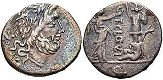 Cloelia (gens) - Quinarius of Titus Cloelius. 98 BC.  Jupiter is portrayed on the obverse.  The reverse depicts Victoria crowning a trophy with a captive at its feet, and a carnyx behind.  It commemorates the victories of Marius against the Teutons.  This coin may have been minted for Marius' veterans.