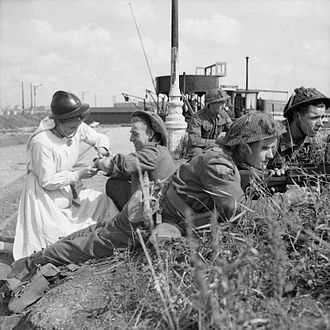 Belgian Resistance - A Resistance nurse provides first aid to a British soldier during the fighting around Antwerp, 1944.