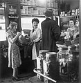 The Reverend Joseph Stephens stops in a grocer's shop in Silvertown, London, to buy some cherries, 1944. D20991.jpg