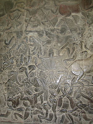 A black stone relief depicting several men wearing a crown and a dhoti, fighting with spears, swords, and bows. A chariot with half the horse out of the frame is seen in the middle.