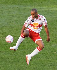 A coloured photograph of a footballer, wearing a white shirt and red kit, adorned with white socks and boots. He is controlling the ball with his right leg from an elevated position.