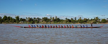 Thirty-five rowers on a long racing pirogue in Laos.jpg