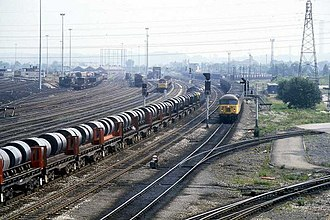 Toton TMD - A classic mid-1980s shot of Toton, showing the Teesside Steelworks/Lackenby sidings – Corby Steelworks train on the up main line headed by a British Rail Class 37, whilst a British Rail Class 56 leaves the North Yard with coal empties on the second down goods line