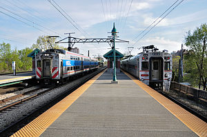 55th–56th–57th Street station - An inbound Metra Electric train of Highliner cars (left) and an outbound South Shore Line train (right) meeting