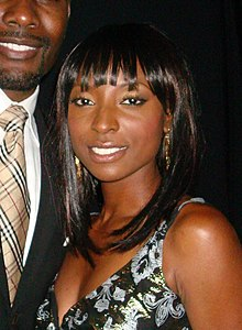 Head and shoulders photo of a dark-skinned woman with long black hair, smiling at the camera, next to a man wearing a suit