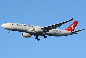 A white and red Turkish Airlines A330-300 with the undercarriages extended over a blue sky.