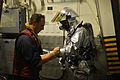 U.S. Navy Hull Maintenance Technician 1st Class Edward Buchanan, left, and Hull Maintenance Technician Fireman Garrett Trotta prepare for a flight deck crash and salvage drill Aug. 7, 2013, aboard the guided 130807-N-YZ751-065.jpg