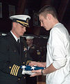 US Navy 030317-N-2174M-002 Kenneth Fredrickson, son of Chief Daniel Fredrickson, receives the National Ensign from Capt. James Colgary, Commanding Officer Naval Submarine Support Facility New London, during a memorial service.jpg